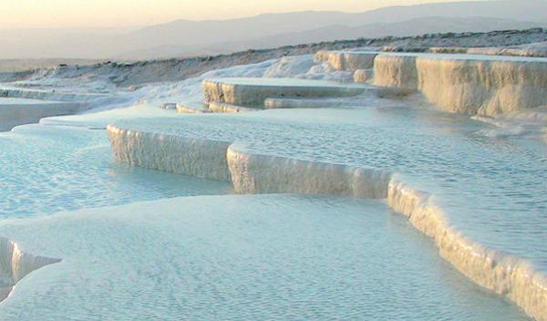 Природные бассейны Памуккале (Турция) В переводе название означает «хлопковый замок». И правда, застывшие белые террасы со струящейся водой напоминают собой пышные хлопья ваты или же айсберги. В течение столетий лечебная вода из термальных источников испаряясь, оставляла белые кристаллы минеральных солей, и таким образом образовывались ослепительные природные ванные.