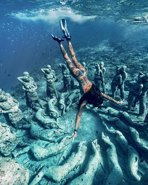 Девушка плавает возле подводной скульптуры